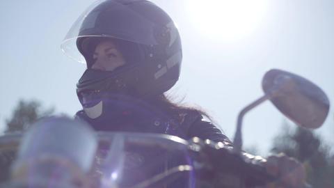 Portrait cute girl wearing black helmet sitting on the motorcycle looking away Live Action
