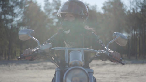Portrait pretty girl wearing black helmet sitting on the motorcycle looking away Live Action