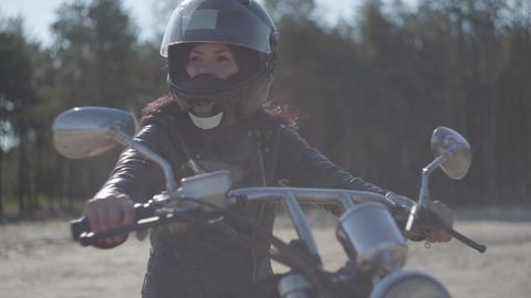 Portrait cute woman wearing black helmet sitting on the motorcycle looking away Live Action