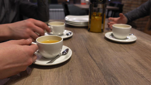 Group of friends people clink and drink tea in the cafe, hands closeup Live Action