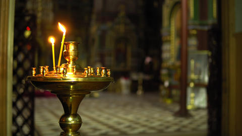 Two candles in the Church on a candlestick on blur church background inside Footage