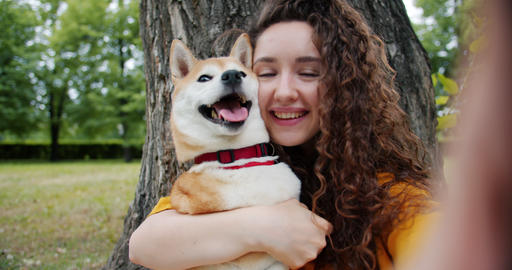 Close-up portrait of girl kissing dog in park taking selfie holding camera Footage