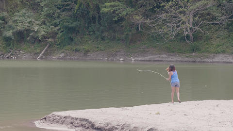 Young woman casting fishing pole in lake water on green nature landscape. Woman Footage