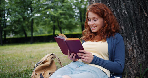 Cheerful redhead girl reading book outdoors in park smiling relaxing on grass Footage