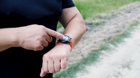athlete runner in black uniform raised his hands with a smart watch and touches, looks and flips Acción en vivo