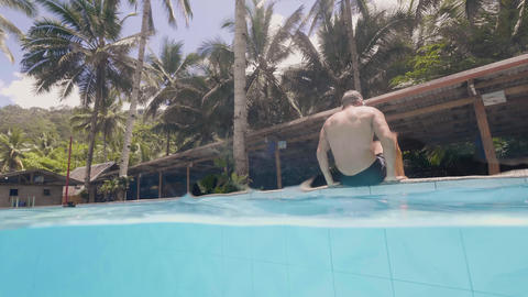 Cheerful man falling in water pool from poolside in summer resort. Happy man Footage
