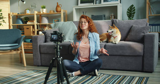 Slow motion of female vlogger recording video at home with cute dog Footage