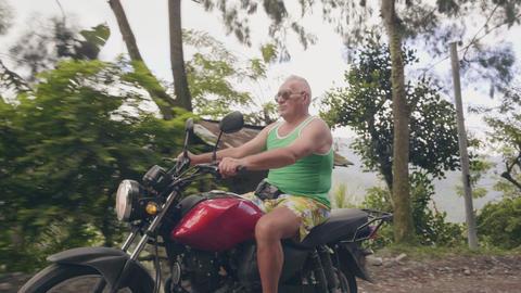 Tourist man traveling on motorcycle on mountain road while moto trip. Senior man Footage