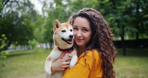 Portrait of pretty girl loving dog owner standing in park with her beautiful pet Footage
