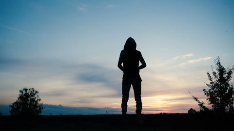 A person in a hood stands alone during sunset in a field against a beautiful sky Footage