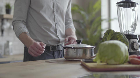 Handsome skill smilling man in the shirt cooking soup in the kitchen. Concept of Live Action