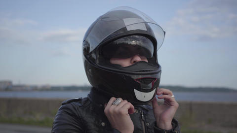 The young woman taking off the motorcycle helmet and looking into the camera Live Action