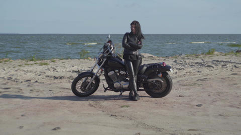 Cute brunette caucasian girl in black leather clothes standing near the Footage