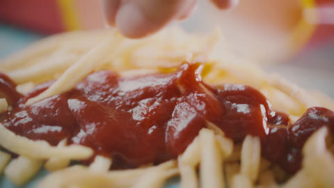 Dipping a piece of french fries or deep-fried potatoes into tomato ketchup Footage