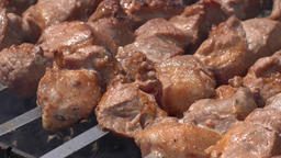 Grilled juicy pork shish kebab cooking on skewers on charcoal grill with fragrant fire smoke Live Action