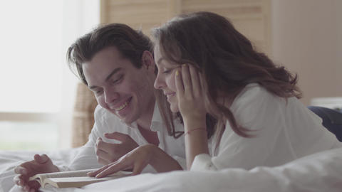 Happy young couple lying on the bed reading the book close-up. Beautiful woman Footage