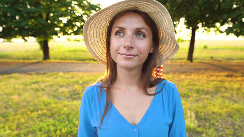 Portrait of pretty woman with hat outdoors in sunny day closeup Footage