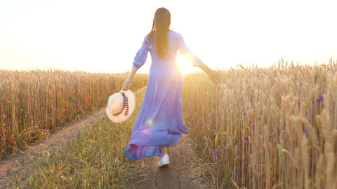 Beautiful woman in a blue dress and hat runs through a wheat field at sunset Footage