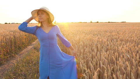 Beautiful woman in a blue dress and hat is spinning in the middle of a wheat Footage