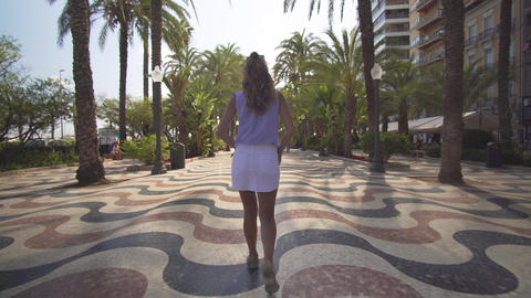 Walk on a sunny day in the city Alicante. Girl walk. Back view Footage