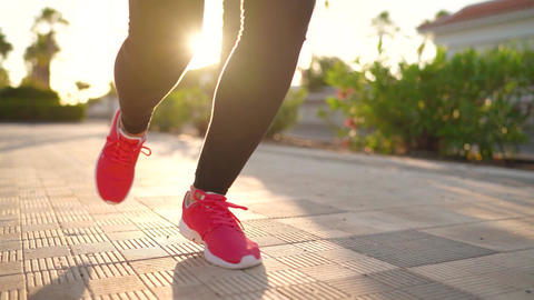 Close up of legs of a woman running along the palm avenue at sunset Footage
