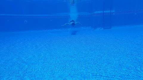 Underwater shooting as a man dives into the pool and swims under the water Footage