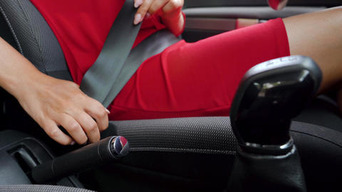 Woman in red dress fastening car safety seat belt while sitting inside of Footage