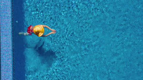 View from the top as a woman in a red swimsuit and a big yellow hat swims in the Footage