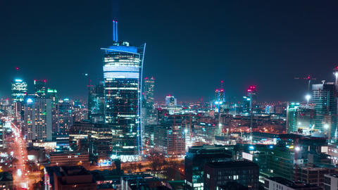 Aerial hyperlapse of Warsaw business center at night: skyscrapers and Palace of Footage