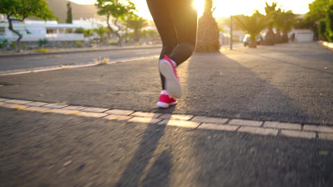 Legs of woman runs down the street among the palm trees at sunset, back view Footage