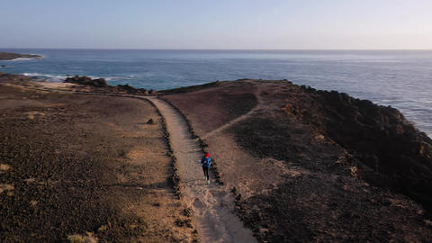 Aerial view of woman runs along the oceanfront nature reserve at sunrise Footage