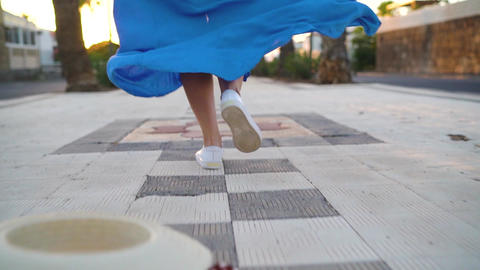 Legs of a woman in a beautiful blue dress running along the palm avenue. Hat Footage