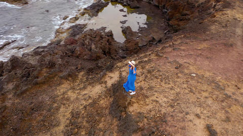 Aerial view of woman in a beautiful blue dress and hat stands on top of a Footage