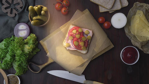 Flat lay of the sandwich with sliced ham, pickle and vegetables on the wooden Footage