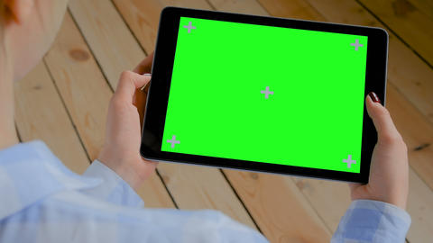 Woman looking at tablet computer with blank green screen - chroma key concept Footage