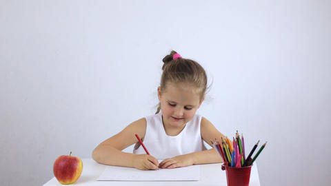 Preschooler girl sits at a desk and diligently draws a drawing Live Action