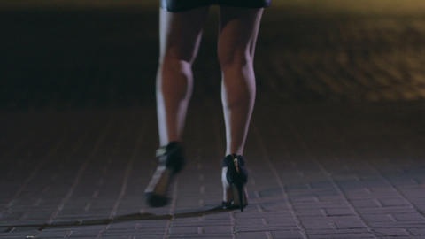 Close up woman's legs dancing on night city street Footage