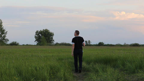 Man walks through the meadow ahead Footage