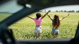 View through car window of women jumping in field Live Action