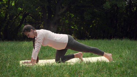 Pregnant woman doing yoga in the park on the carpet, standing on one knee, doing Footage