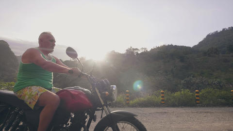 Adult man riding on motorcycle on countryside while summer moto travel, sunshine Live Action