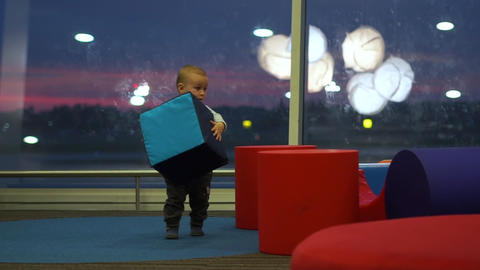 Little cute boy playing with big cubes in a children's play area at the airport Live Action