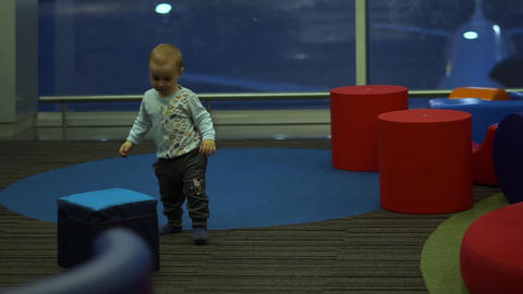 Boy playing with big cubes in a children's play area at the airport, slow motion Footage