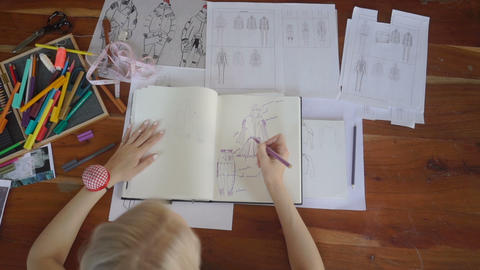 Top view of the designer with a pen, designing and sketching new collection Footage