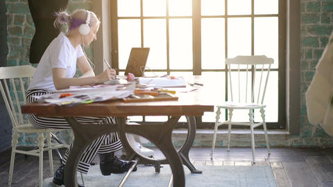 Young professional fashion designer drawing sketches for clothes in workplace Live Action