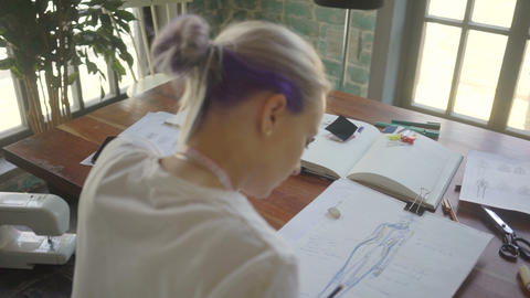 Young fashion woman designer drawing design sketch working in her manufacturing Footage