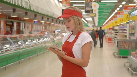 Supermarket clerk using apps on a digital tablet, innovative technology and work Footage
