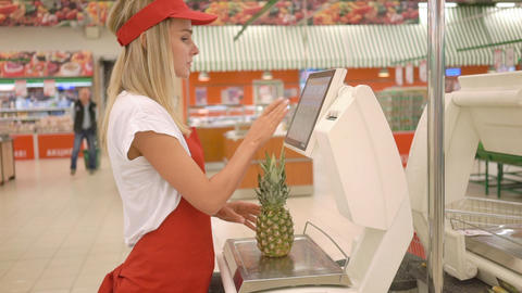 Saleswoman in red apron weighing fresh pineapple on electronic scales with touch Footage