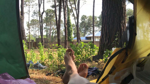 female feet relaxing in camping tent Live Action