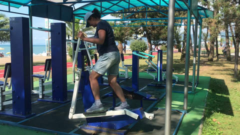 Overweight woman doing cardio exercises on ellipsoid at the gym outside in park Footage